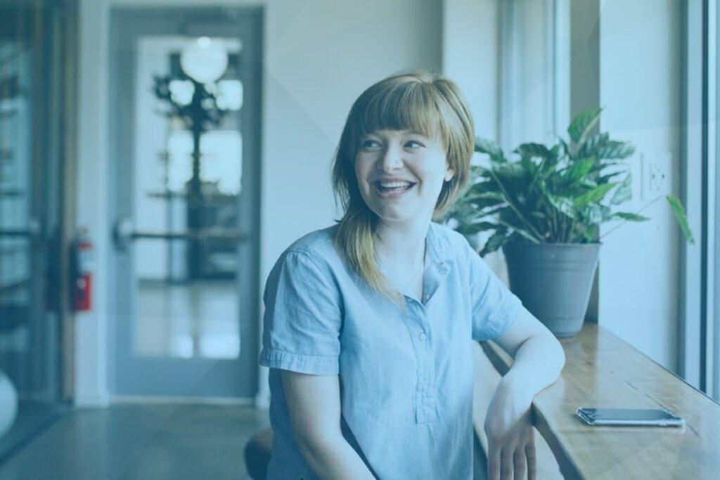 femme autiste souriante accoudée à un bureau