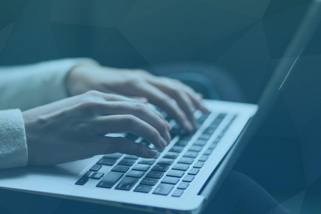 Une personne experte écrit sur son ordinateur en collaboration avec une personne autiste/TSA